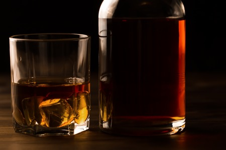 shot: glass of whiskey with ice and a bottle on a wooden table. Cognac, brandy. Stock Photo