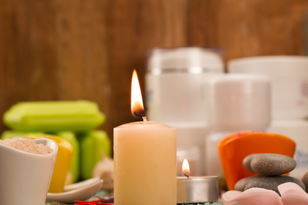 Spa composition with sea salt, candles, soap, shells, creams for face on wooden background. Aromatherapy. Standard-Bild