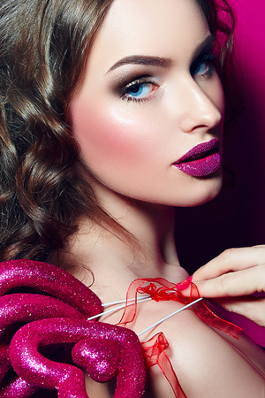 glamour girl: Glamour girl with pink make up holding a heart in his hands. Stock Photo