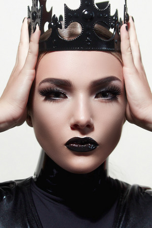 Black queen. Trendy hairstyles. Beautiful make-up. Beautiful face. Beautiful girl. A stern look. Black crown. The girl's face.