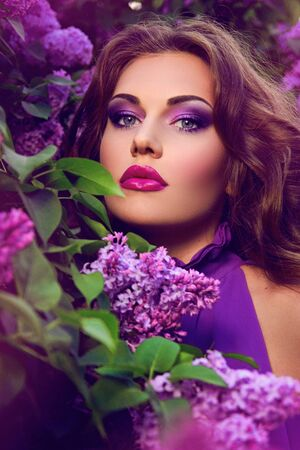 makeup eyes: The girls face. Beautiful girl with flowers. Lilac. Blue dress. Stock Photo