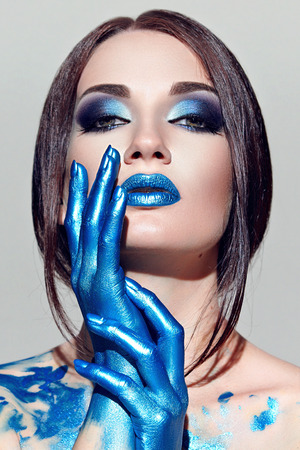 The girls face with blue makeup with white paint. Hands painted in blue paint. Long straight black hair. Stock Photo