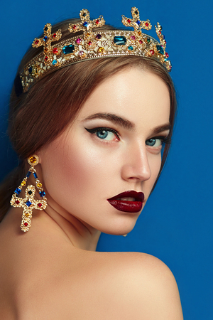 Girl with a golden crown and golden earrings. The crown with precious stones, diamond, sapphire. Earrings in the shape of a cross. Brown-haired girl. Blue background.