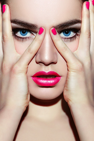 pink lips: Hands on the face of the girl. The girl with light make-up with pink lips, covers his face with his hands.