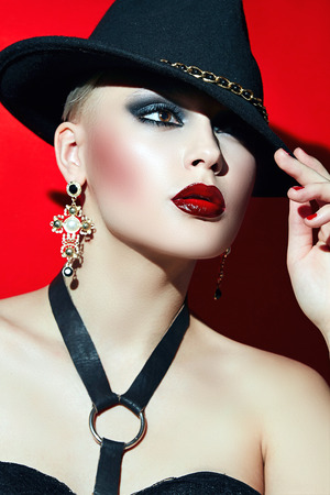 red corset: Rock girl in a black hat with red lips and dark eyes in a corset. Stock Photo
