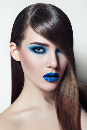 hair cover: Fashionable girl with brown hair smooth silky straight hair. Blue ink and a blue lipstick. Hair cover one eye. Stock Photo