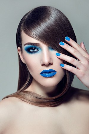 silky hair: Fashionable girl with brown hair smooth silky straight hair. Blue ink and a blue lipstick. Hair cover one eye. Stock Photo