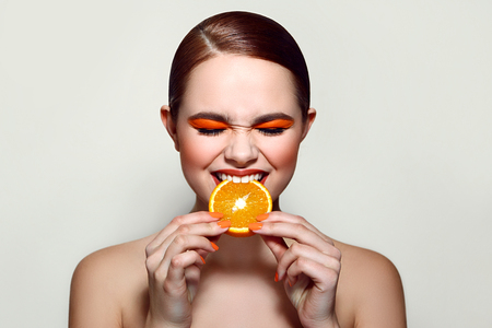 without clothes: Sour orange. The girl is tasting the fruit. It keeps the fruit with both hands. Squints. Closed eyes. Orange shadow on the eyes. Orange fingernails. Orange, lemon, citrus.