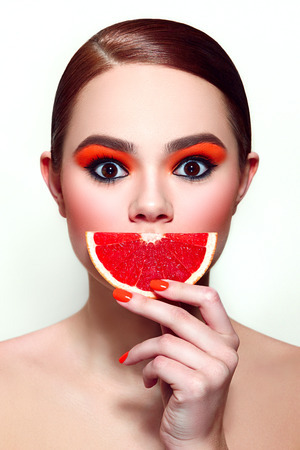 without clothes: Red grapefruit. Girl holding fruit in her hand in the face. Eyes wide open. Orange shadow on the eyes. Orange fingernails.