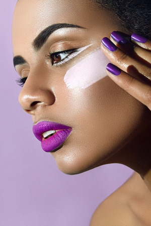 half turn: Mulatto with purple lipstick and purple nails and white paint smear on the cheek.