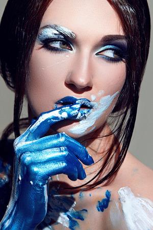 Il viso della ragazza con il trucco blu con vernice bianca. Le mani dipinte di vernice blu. Lunghi capelli neri e lisci. Archivio Fotografico