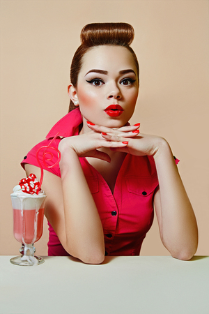 Girl in retro style pin-up style, in a bright dress with red lips and rosy cheeks on a colored background with a milkshake and a pink straw.