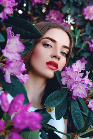 Beautiful girl in a bright dress with flowing hair on the background of shrubs with large pink flowers and large leaves. Stock Photo