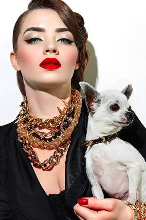 Girl with a small dog with red lips gold ornaments in the style of steam-punk. Military fashion.
