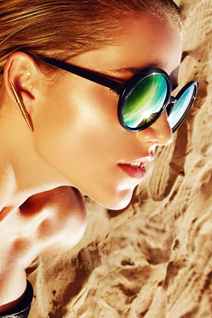 Tanned girl on the sand in sun glass with wet hair and gold jewelry. Stock Photo