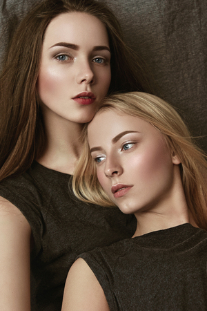 Two girls. Bright makeup. Sisters. Brunette and blonde. In a studio. Cloth background. Girls dressed in shirts.