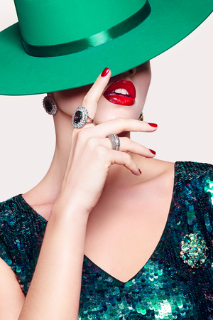 Girl in shiny green dress with green hat with beautiful decorations with red lips. Mysterious stranger. Girl hides the face.
