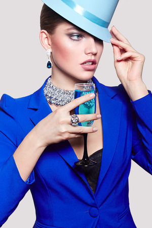 Fashionable young beautiful girl in a blue jacket with a cocktail in hand and wearing a hat on her head.