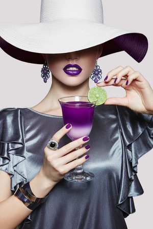 Girl in a white hat with a wide brim pet cocktail with lime. Fashionable stranger woman hiding her eyes under the hat. Gray dress with brilliant decorations. Colorful cocktail.