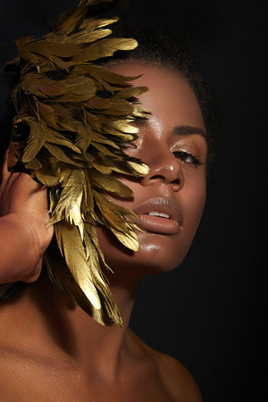 black makeup: The black beautiful girl with golden feathers, full lips, with golden skin. Stock Photo