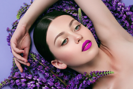 Beautiful young girl is surrounded by purple flowers. Blue flowers. Lilac lipstick. Cosmetic products for skin care.