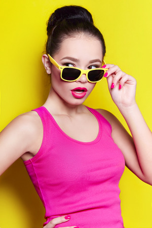 Beautiful young smiling girl in a pink shirt and with a pink lipstick with the collected hair in a bun with yellow sunglasses. The girl on a yellow background in the studio. Stock Photo