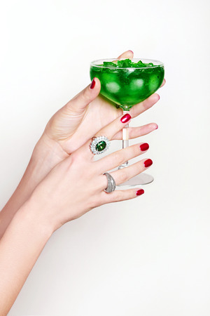 woman's hands: Glass with a cocktail from the female hands. Green drink with ice. Precious rings on the fingers.