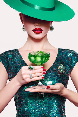 Girl in a green hat with a cocktail in hand. Green party dress. Absinthe ice. Stock Photo