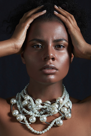 Face girl black woman close up. Beautiful big white beads around the neck of the girl. The girl looks straight into the camera, her hands holding her head. Stock Photo