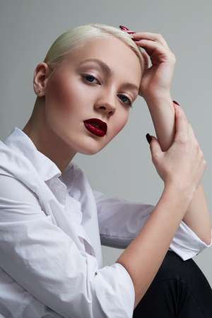 Girl blonde with short hair wearing a white shirt sits sideways in the studio on a white background. Young girl looking at the camera. Office employee. Business woman. Girl with red lipstick. Stock Photo
