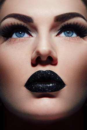 Girls face close up. Black lipstick on the lips plump. Girl with blue eyes looking up. Make-up in black tones. Sequins on the lips. Smooth skin.