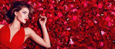 バレンタインの日。愛情のある女の子。赤いバラの花びらで床に横になっている赤いドレスの女の子。赤いバラの花びらの背景。美しい少女の唇に赤い口紅。