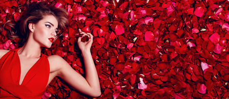 バレンタインの日。愛情のある女の子。赤いバラの花びらで床に横になっている赤いドレスの女の子。赤いバラの花びらの背景。美しい少女の唇に