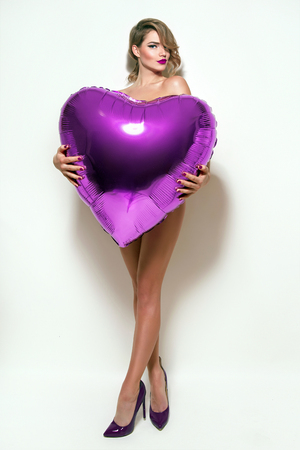 Valentine's Day. Nude beautiful girl with retro hairstyle hiding behind huge volume purple heart. Inflatable balloon in shape of heart in hands at girl. Naked girl in studio on a white background.