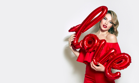 Valentines Day. Word love letters from the inflatable. Girl holding a big word love.Girl with retro hairstyle in red dress in red high heels in studio on a white background.