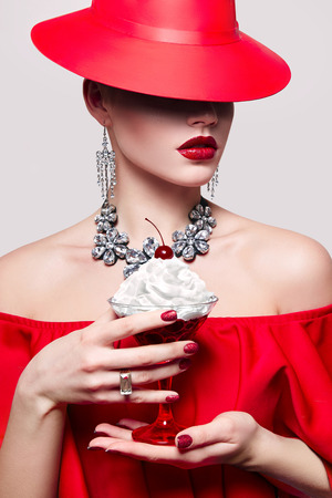Girl in red hat and red dress holding a cocktail glass in her hands. Cocktail with cream and cherries. The girl's face is covered by hat. Red lipstick on the lips. Advertising of alcoholic beverage. Stock Photo