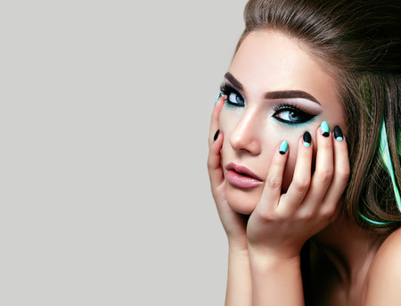 The girls face with bright makeup closeup on a white background. Black and white nails. Manicure. Fingers in the girls face. The volume hairstyle. The girl looks into the camera.