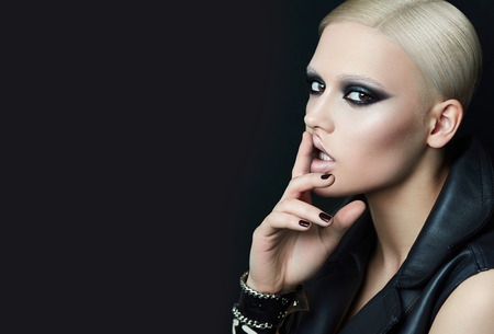 Blond girl in a rock style with makeup smoky ice in the studio on a black background.Girl punk dressed in leather jacket.The bracelet on her hand girl. Touching the face with fingers.