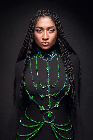 African-American girl in a black dress in the big emerald necklace on a black background. Black girl in long hair in braids.