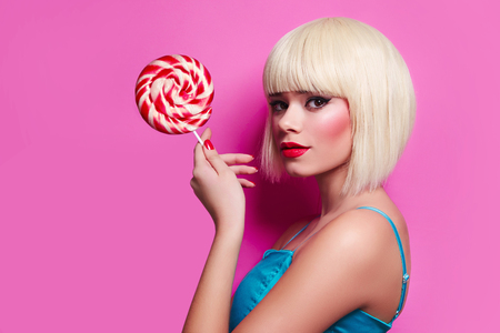 The girl with a sweet face in white wig with a lollipop in her hands on a pink background. Multicolored gumdrop in the hands of women.