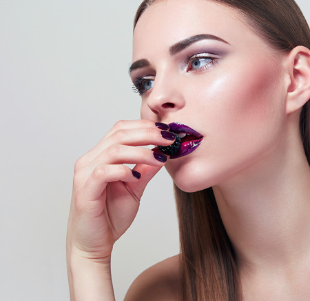 The girl in a beautiful face eating a berry. Beautiful expressive makeup on the face of the girl. The girls face close up. Lilac lipstick. The girl in the studio on a white background.
