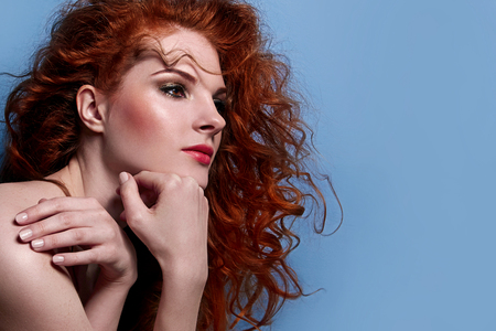 Beautiful red-haired cute girl with curly hair, in profile view, looking thoughtful. The girl with a gentle makeup on her face. Freckles on the face of the girl. Stock Photo