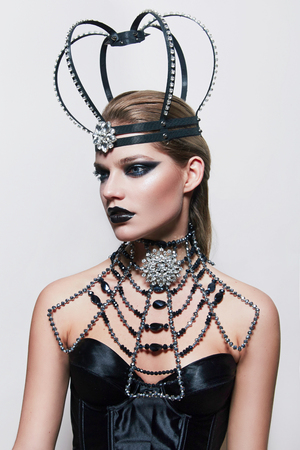 A girl with an unusual crown with jewels and a large necklace sitting in the studio. Girl dressed in a black corset. On the girls head with a large crown jewel in the middle of the forehead. Stock Photo