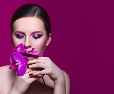 A beautiful girl is holding a lilac orchid in her hands in front of her face. Blue beautiful fresh natural flower in hands of the girl. Portrait of a girl with flowers in studio on a pink background.