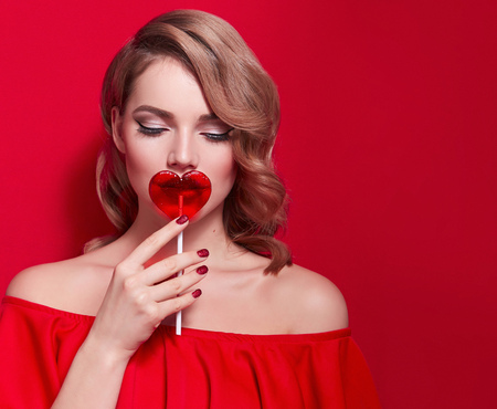 The girl in a red dress on a red background in the studio. Blonde girl holding a red heart-shaped lollipop. Valentine's Day. Advertising. Girl holding a lollipop in his mouth. Stock Photo
