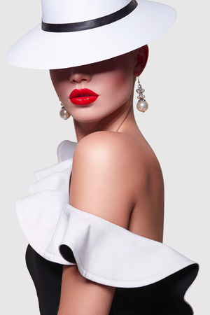 A girl in a white hat and in black and white attire with a shaft in the studio on a white background. A girl with red lips and smooth skin stands sideways.