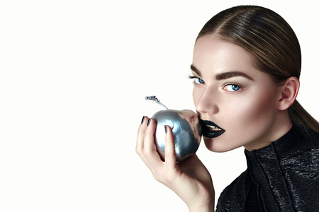 A beautiful girl in a black shiny dress with black lipstick and a smooth hairdo with a silver glossy apple in her hand. Studio, background. Advertising cosmetics, jewelry.