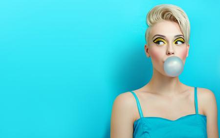 Chica de moda con un corte de pelo estilo infla una goma de mascar. La chica en el estudio sobre un fondo azul. La cara de la chica con el maquillaje brillante y amarillo con sombras negras en los ojos. Foto de archivo - 75254973