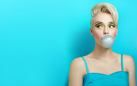 Fashionable girl with a stylish haircut inflates a chewing gum. The girl in the studio on a blue background. The girls face with bright makeup and yellow with black shadows on the eyes.