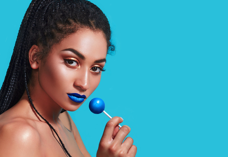 Beautiful african american girl in studio on a blue background. Hair of the pigtail, tail. Smooth, shiny skin. She holds a blue candy in his hand. Blue lipstick. Cosmetics, advertising.